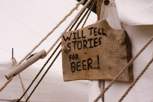 Sign pegged on a tent: will tell stories for beer
