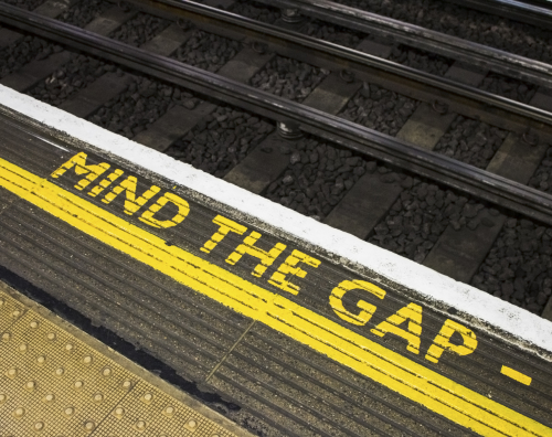 Mind the gap sign on the floor of a London Underground station with a railway line beyond