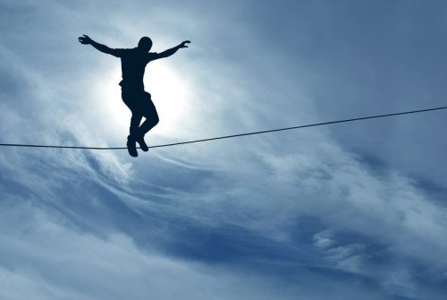 Silhouette of a man balancing on a tightrope