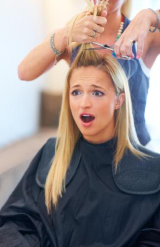 Shocked young woman having a bad haircut at the salon