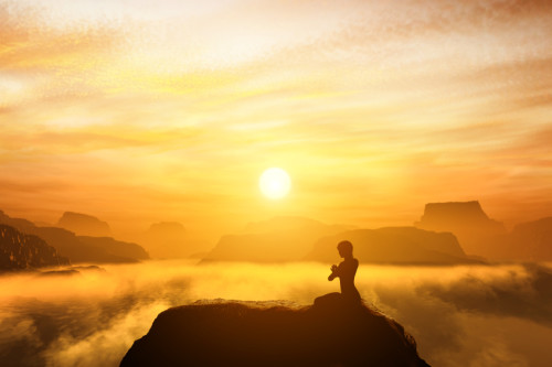 Peace of mind - Woman meditating, sitting in a yoga position on the top of a mountain above clouds at sunset.