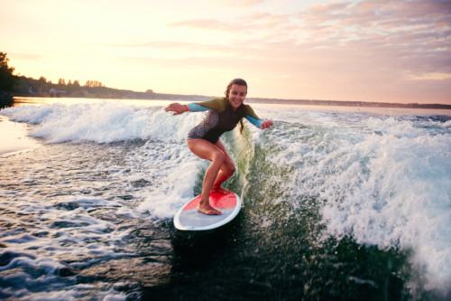 Young woman surfboarding at summer resort
